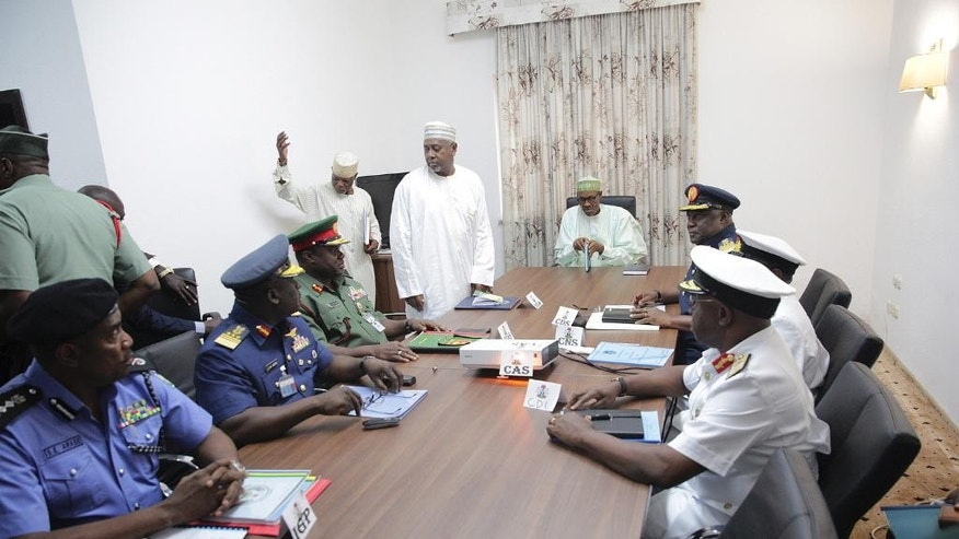 Nigeria President,  Muhammadu Buhari, centre, is seated before a meeting with service chiefs in Abuja Nigeria, Tuesday, June 2, 2015.  The Nigerian President held his first meeting with military service chiefs, amid speculation that there will be changes in the war against Boko Haram. (AP Photo/Bayo Omoboriowo)