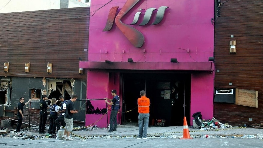 FILE - In this Jan. 27, 2013 file photo, police investigators inspect the entrance of the Kiss nightclub after a fire inside the club in Santa Maria city, Rio Grande do Sul state, Brazil. A court on Wednesday, June 3, 2015 convicted and sentenced to one year in jail two of the eight firefighters on trial for the nightclub fire that killed more than 200 people. The firefighters had been charged with negligence and with falsifying public documents related to the club's fire permit. (AP Photo/Nabor Goulart, File)