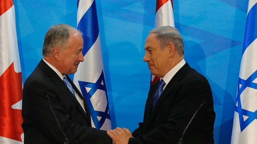 Israel's Prime Minister Benjamin Netanyahu, right, and Canada's Foreign Minister Robert Douglas Nicholson, shake hands after their meeting in Jerusalem Wednesday, June 3, 2015. (Ammar Awad/Pool Photo via AP)