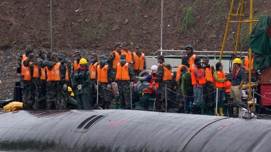 Chinese soldiers stand near a wrapped body as rescuers work on the capsized ship, center, on the Yangtze River in central China's Hubei province Wednesday, June 3, 2015. Hopes dimmed Wednesday for rescuing more than 400 people still trapped in the capsized river cruise ship that overturned in stormy weather, as hundreds of rescuers searched the Yangtze River site in what could become the deadliest Chinese maritime accident in decades. (AP Photo/Andy Wong)