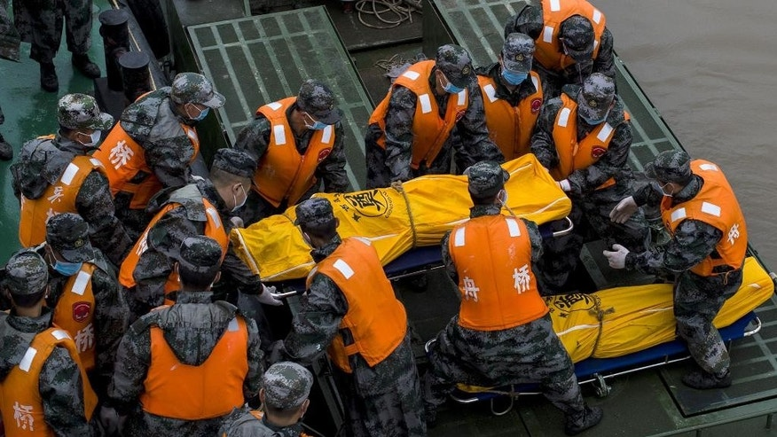 In this photo released by China's Xinhua News Agency, rescuers try to carry a victim's body at the site of the overturned ship in the Jianli section of the Yangtze River, central China's Hubei Province Wednesday, June 3, 2015. Hopes dimmed Wednesday for rescuing more than 400 people still trapped in the capsized river cruise ship that overturned in stormy weather, as hundreds of rescuers searched the Yangtze River site in what could become the deadliest Chinese maritime accident in decades. (Xiao Yijiu/Xinhua via AP) NO SALES
