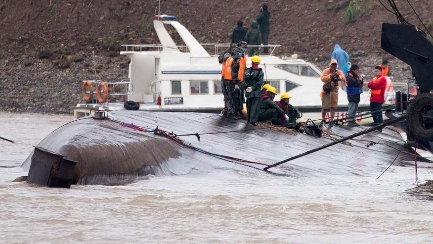 Chinese soldiers stand as rescuers conduct a search and rescue operation on the capsized ship, center, on the Yangtze River in central China's Hubei province Wednesday, June 3, 2015. Hopes dimmed Wednesday for rescuing more than 400 people still trapped in a capsized river cruise ship that overturned in stormy weather, as hundreds of rescuers searched the Yangtze River site in what could become the deadliest Chinese maritime accident in decades. (AP Photo/Andy Wong)
