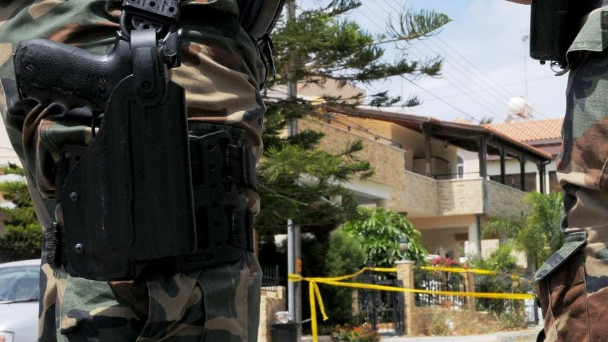 Riot police stand guard outside of the house, left behind tree, which was discovered to contain some two tons of a chemical compound in southern costal city of Larnaca, Cyprus, on Saturday, May 30,  2015.  A Cyprus court has ordered a 26-year-old Lebanese-Canadian man to remain in police custody for eight days after two tons of a chemical compound that can be turned into an explosive was discovered at his home.  (AP Photo/Petros Karadjias)