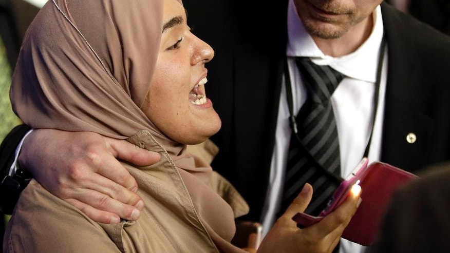 A security officer holds a young women who shouts after a press conference as part of a meeting between German Chancellor Angela Merkel and the President of Egypt Abdel Fattah el-Sissi at the chancellery in Berlin, Germany, Wednesday, June 3, 2015. (AP Photo/Michael Sohn)