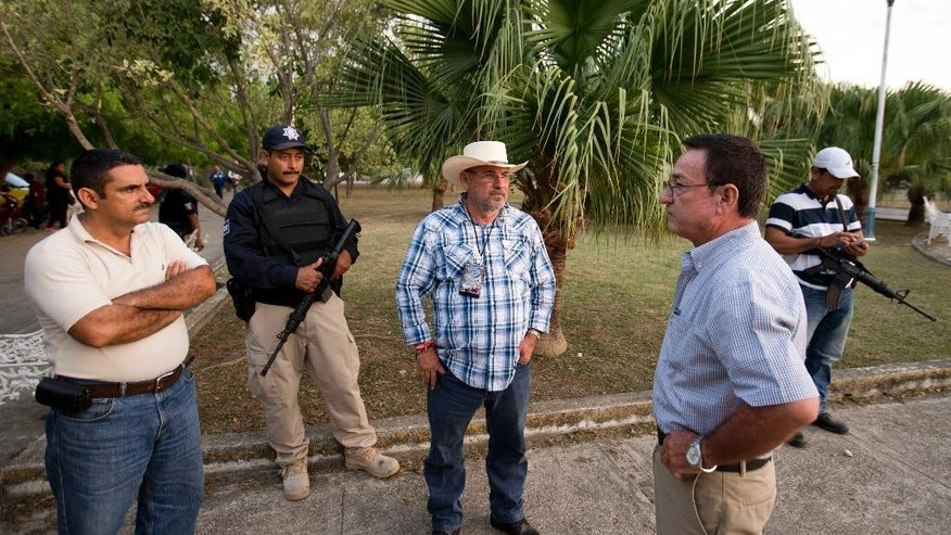 In this May 21, 2015 photo, congressional candidate, former self-defense group leader Hipolito Mora, center, waits to start a campaign meeting with residents in Coahuayana, Michoacan state, Mexico. For his security, Mora is flanked by two armed men; a rural police officer, left, and a vigilante. At far left is his deputy Jose Luis Torres, and at right is a supporter who introduced himself and his family before the meeting. After helping bring down the Knights Templar cartel with a vigilante uprising in 2013, twice landing in jail and losing his own son to violence, the 59-year-old man now is leading a different sort of campaign by running for Congress in Mexico's midterm elections on June 7. (AP Photo/Eduardo Verdugo)