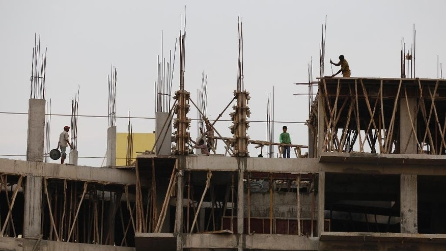Indian laborers work at an under construction residential building in Bangalore, India, Tuesday, June 2, 2015. India's central bank cut a key interest rate by a quarter percentage point Tuesday, the third such reduction this year in support of government efforts to boost growth. (AP Photo/Aijaz Rahi)