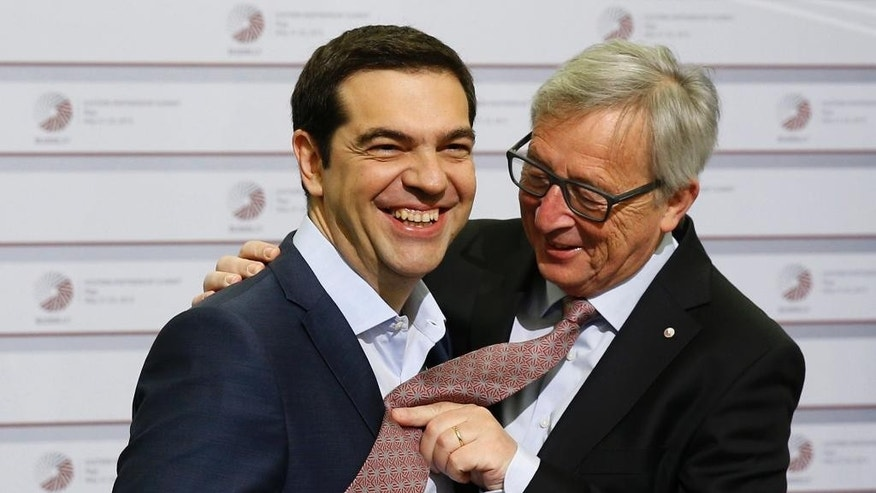 FILE - In this Friday, May 22, 2015 file photo, European Commission President Jean-Claude Juncker, right, pushes his tie up against the shirt of Greek Prime Minister Alexis Tsipras during a recent meeting in Riga, Latvia. Tsipras is heading to Brussels Wednesday, June 3, 2015 to discuss his radical-left government's proposal for a long-delayed deal with Greece's creditors that Athens hopes will unlock vitally needed bailout funds. Tsipras was invited to Brussels by Juncker, with whom he was to meet for talks Wednesday evening, a Greek government official said. (AP Photo/Mindaugas Kulbis, File)