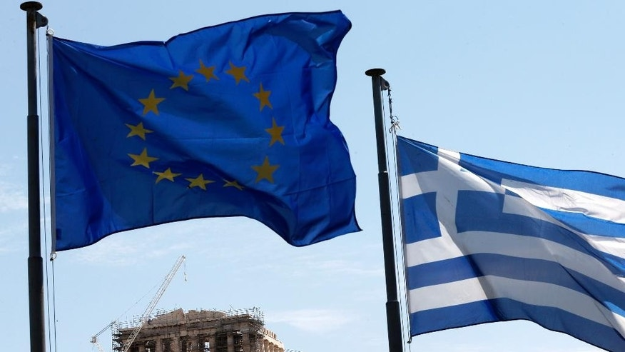 A Greek and a European Union flag billow in the wind as the ruins of the fifth century BC Parthenon temple are seen in the background on the Acropolis hill, Athens, Wednesday, June 3, 2015. Greece's prime minister was heading to high-level meetings in Brussels on Wednesday to try to persuade the country's creditors to accept a proposal that might unlock much-delayed bailout loans and save the country from financial disaster. (AP Photo/Petros Giannakouris)
