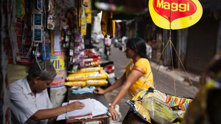 A basket filled with packaged food hangs with a 'Maggi' sign on it outside a shop in New Delhi, India, Wednesday, June 3, 2015. Indian shopkeepers withdrew the popular brand of instant noodle from their shelves Wednesday after tests revealed the snack contained lead above permissible levels. (AP Photo/Tsering Topgyal)