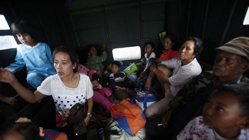 Villagers sit in a truck as they evacuate their homes on the slope of Mount Sinabung in Karo, North Sumatra, Indonesia, Wednesday, June 3, 2015. Indonesia has raised the alert status of the 2,600-meter (8,530-foot) -high volcano in the western part of the country to the highest level following a sharp increase in activity, and urged residents living within a radius of 7 kilometers (4 miles) south and southeast of the crater to evacuate. (AP Photo/Binsar Bakkara)