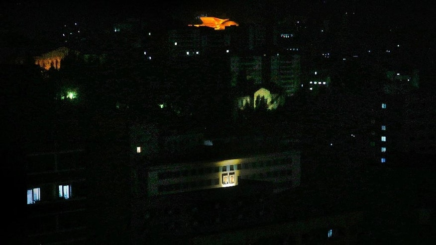 In this May 5, 2015, photo, portraits of late North Korean leads Kim Il Sung and Kim Jong Il, are illuminated on a building facade amongst he rest of Pyongyang city which is mostly in darkness, in North Korea. North Korea is racing to boost its electricity supply by 20 to 50 percent ahead of a major anniversary later this year and is pushing alternative resources like solar, which is already used extensively in the countryside, to ease its chronic shortages of energy. (AP Photo/Wong Maye-E)