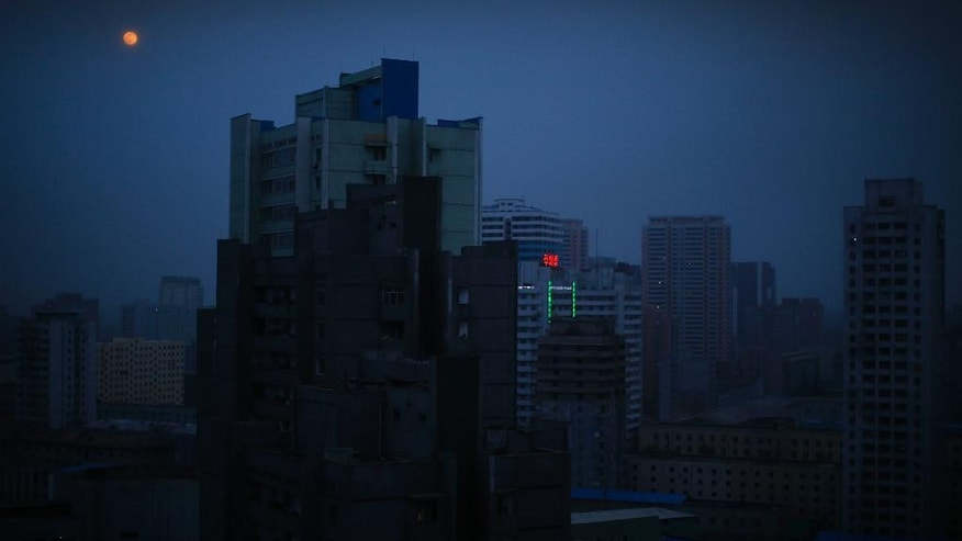 In this May 3, 2015, photo, the moon hangs over Pyongyang city which is mostly in darkness, in North Korea. North Korea is racing to boost its electricity supply by 20 to 50 percent ahead of a major anniversary later this year and is pushing alternative resources like solar, which is already used extensively in the countryside, to ease its chronic shortages of energy. (AP Photo/Wong Maye-E)