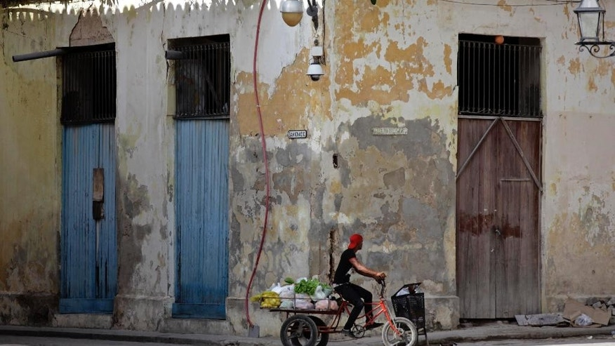 In this May 24, 2015 photo, a vegetable vendor cycles through Cathedral Square in Old Havana, Cuba. In some destinations, tourist areas are located far from the rhythms of everyday life. But visitors who wander through Old Havana or Habana Vieja as locals call it, canít help but get a sense of how ordinary Cubans live. (AP Photo/Desmond Boylan)
