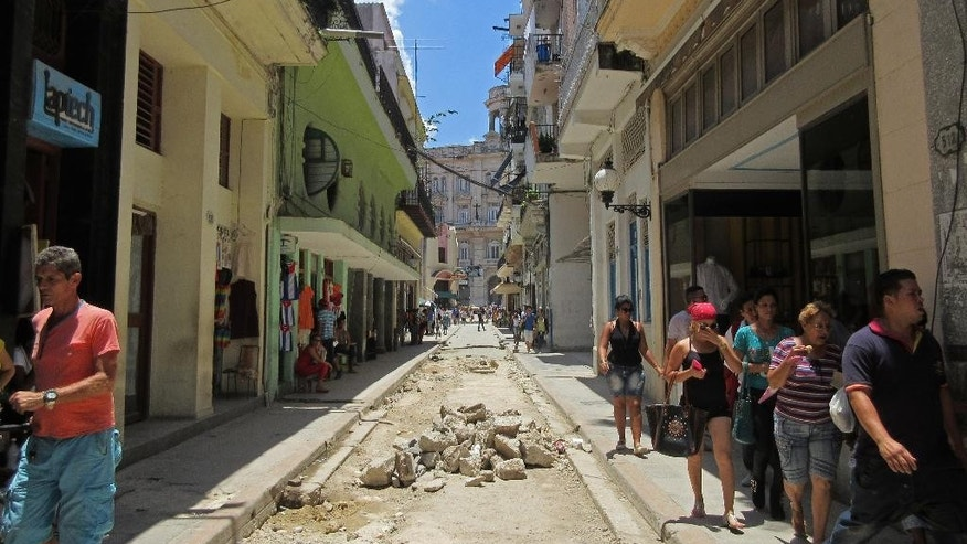 In this May 17, 2015 photo, pedestrians walk on a narrow street in Old Havana, Cuba. It's not unusual to see the sky through a roofless stone facade or piles of rubble in the street. But other sites have been beautifully restored, especially around the squares in the eastern half of the neighborhood bordering the water. (AP Photo/Beth J. Harpaz)