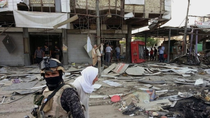A member of the Iraqi security forces stands guard at the site of a car bomb attack as civilians watch the damaged area in Baghdad, Iraq, Tuesday, June 2, 2015. Police officials said the car went off inside the parking lot of a Qadouri restaurant in eastern Baghdad on Tuesday afternoon, killing several people. (AP Photo/Hadi Mizban)
