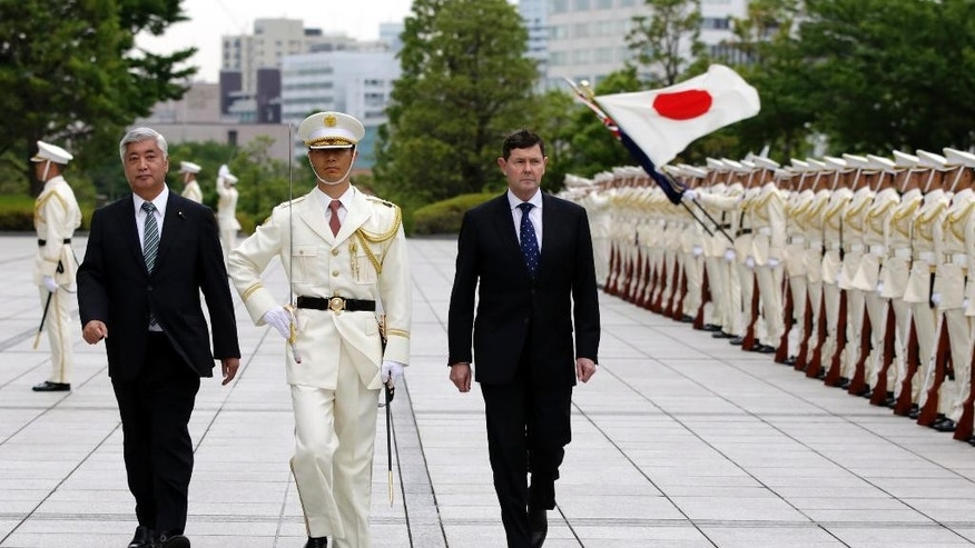 Australian Defense Minister Kevin Andrews, right, and his Japanese counterpart Gen Nakatani, left, inspect an honor guard at Defense Ministry in Tokyo, Wednesday, June 3, 2015. Andrews is here to follow up on a possible submarine development. (AP Photo/Eugene Hoshiko)