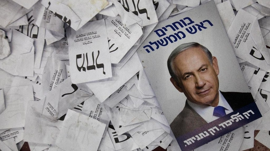 FILE - In this Wednesday, March 18, 2015 file photo, an election campaign poster with the image of Israeli Prime Minister Benjamin Netanyahu lies among ballot papers at his party's election headquarters, in Tel Aviv.  These are tough times for political pollsters. In recent elections in Israel, Britain and Poland pre-election polls failed spectacularly to predict election results, sending shock waves through entire nations on election night. Now many research pollsters are analyzing these fiascos in search of ways to do better in the future. In Britain, Prime Minister David Cameron's Conservatives won a clear victory on May 7 after polls had predicted a near tie with Labour, generating expectations of a hung parliament. A day after the election the British Polling Council launched an independent inquiry into the polls' inaccuracies. ( (AP Photo/Dan Balilty, File)