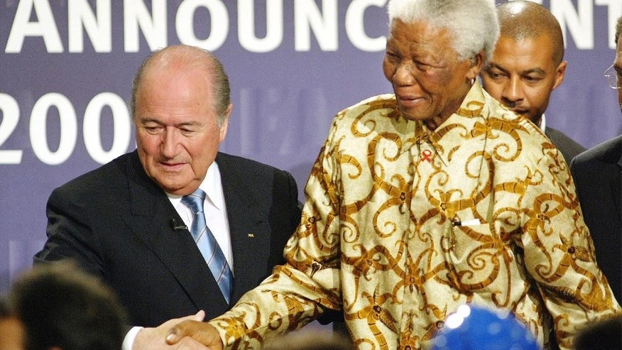 FILE - In this Saturday, May 15, 2004 file photo former South African President Nelson Mandela, right, is lead to the podium by FIFA President Sepp Blatter, of Switzerland, left, after learning that South Africa will host the 2010 FIFA World Cup, in Zurich, Switzerland.  (AP Photo/Michael Probst, File)