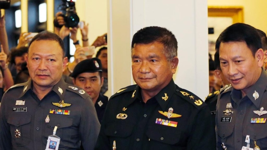 Senior adviser to the Royal Thai Army Lt. Gen. Manas Kongpaen, center, arrives at the police headquarters in Bangkok, Thailand, Wednesday, June 3, 2015. A senior Thai army officer has turned himself in over his alleged involvement in a human trafficking scandal, marking the first arrest of a military official since the investigation started last month. (AP Photo/Sakchai Lalit)