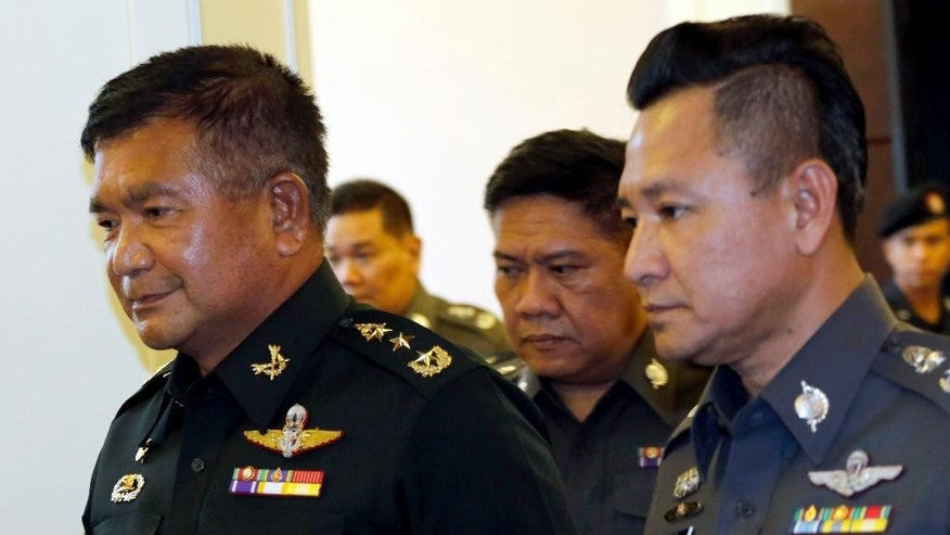 Senior adviser to the Royal Thai Army Lt. Gen. Manas Kongpaen, left, leaves the police headquarters in Bangkok, Thailand, Wednesday, June 3, 2015. A senior Thai army officer has turned himself in over his alleged involvement in a human trafficking scandal, marking the first arrest of a military official since the investigation started last month. (AP Photo/Sakchai Lalit)