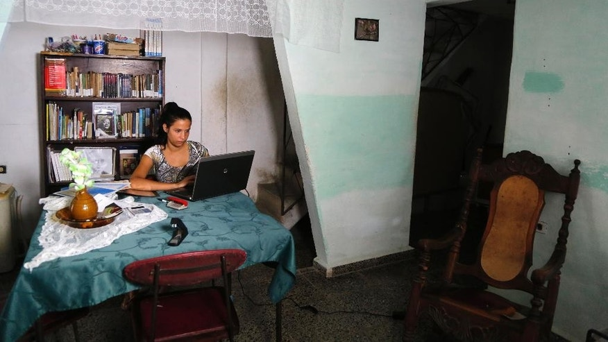"In this May 22, 2015 photo, Eleyn Ponjuan, who is taking a course in independent journalism led by U.S. professors via video link inside the U.S. Interests Section, works on her laptop at home in Havana, Cuba.  ""I don't consider myself counter revolutionary, on the contrary,"" she said in her cramped house in a poor section of Havana where she also runs a free community library out of her living room. ""I just a want a change for the better for the country,"" Ponjuan said.  (AP Photo/Desmond Boylan)"