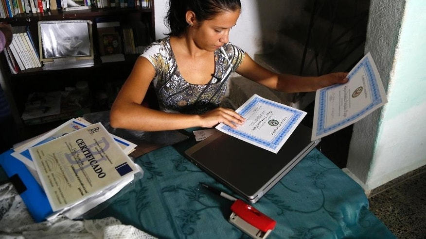 "In this May 22, 2015 photo, Eleyn Ponjuan, who is taking a course in independent journalism led by U.S. professors via video link inside the U.S. Interests Section, arranges certificates for her completed English and journalism courses, at home in Havana, Cuba.  ""These courses are a very good opportunity for us, for those who don't have any resources, who don't have work, and I don't think there is anything wrong with that,"" said Ponjuan. (AP Photo/Desmond Boylan)"