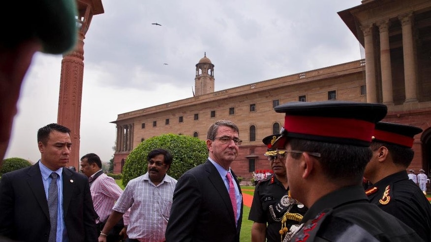 U.S. Defense Secretary Ashton Carter speaks to a soldier after receiving a ceremonial welcome in New Delhi, India, Wednesday, June 3, 2015. Carter is in India on a three-day visit where he is expected to sign a ten-year defense pact. (AP Photo/ Saurabh Das)