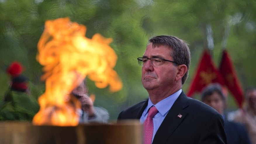 U.S. Defense Secretary Ashton Carter pays homage at the India Gate war memorial in New Delhi, India, Wednesday, June 3, 2015. Carter is in India on a three-day visit where he is expected to sign a ten-year defense pact. (AP Photo/ Manish Swarup)
