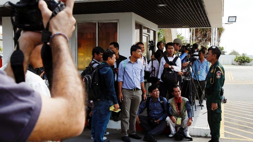 Journalists talk with airport security personnel, right, as they wait for the transportation of refugees from Australia outside of Phnom Penh International Airport, in Phnom Penh, Cambodia, Thursday, June 4, 2015. Four asylum seekers rejected by Australia have arrived in Cambodia, becoming the first to leave the Pacific island nation of Nauru under a deal that allows refugees rejected by Australia to be resettled in the Southeast Asian country. (AP Photo/Heng Sinith)