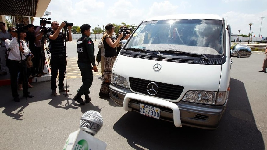 A van drives four refugees from Australia out of Phnom Penh International Airport, in Phnom Penh, Cambodia, Thursday, June 4, 2015. Four asylum seekers rejected by Australia have arrived in Cambodia, becoming the first to leave the Pacific island nation of Nauru under a deal that allows refugees rejected by Australia to be resettled in the Southeast Asian country. (AP Photo/Heng Sinith)