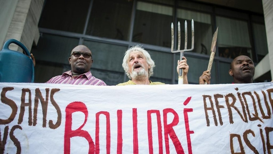 Activists demonstrate in front of conglomerate Bollore headquarters in Puteaux near Paris, France, calling on Bollore to return land, or compensate farmers, over disputed concessions for plantations in Cambodia and three African countries, Thursday, June 4, 2015.  Bollore is the largest shareholder of Socfin, which has been accused by activists of land grabs in Cambodia, Liberia, Cameroon and Ivory Coast. (AP Photo/Kamil Zihnioglu)