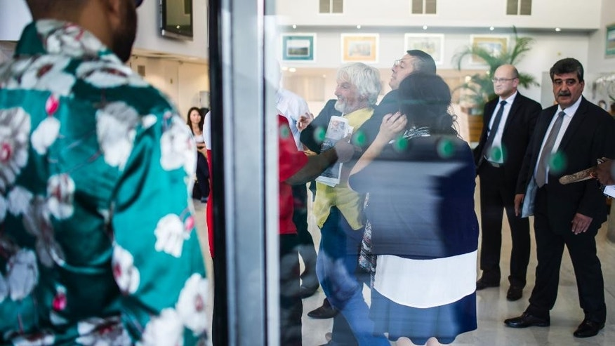 Activists try to invade the lobby of conglomerate Bollore headquarters in Puteaux near Paris, France, calling on Bollore to return land, or compensate farmers, over disputed concessions for plantations in Cambodia and three African countries, Thursday, June 4, 2015.  Bollore is the largest shareholder of Socfin, which has been accused by activists of land grabs in Cambodia, Liberia, Cameroon and Ivory Coast. (AP Photo/Kamil Zihnioglu)