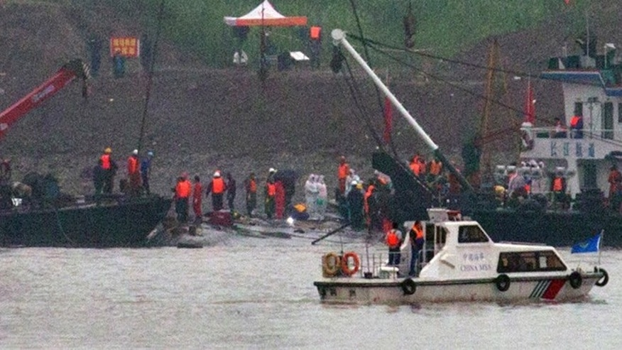 June 4, 2015: A marine boat patrols past as rescuers work on the capsized ship, center, on the Yangtze River in Jianli county of southern Chinas Hubei province, as seen from across the river from Huarong county of southern Chinas Hunan province. Rescuers cut into the upside-down hull of the river cruise ship and pulled out drowned passengers early Thursday.