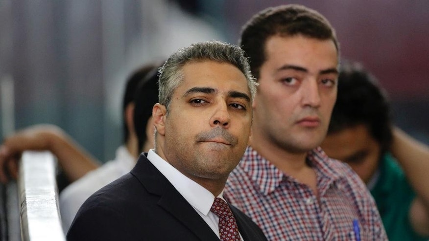 Canadian Al-Jazeera English journalist Mohammed Fahmy, left, and his Egyptian colleague Baher Mohammed, right, listen in a courtroom, in Tora prison, in Cairo, Egypt, Thursday, June 4, 2015. Fahmy is being tried along with Egyptian producer Baher Mohammed on charges accusing them of being part of a terrorist group and airing falsified footage intended to damage national security. The retrial in a case widely criticized by human rights organizations and media groups has been postponed to June 11. (AP Photo/Amr Nabil)