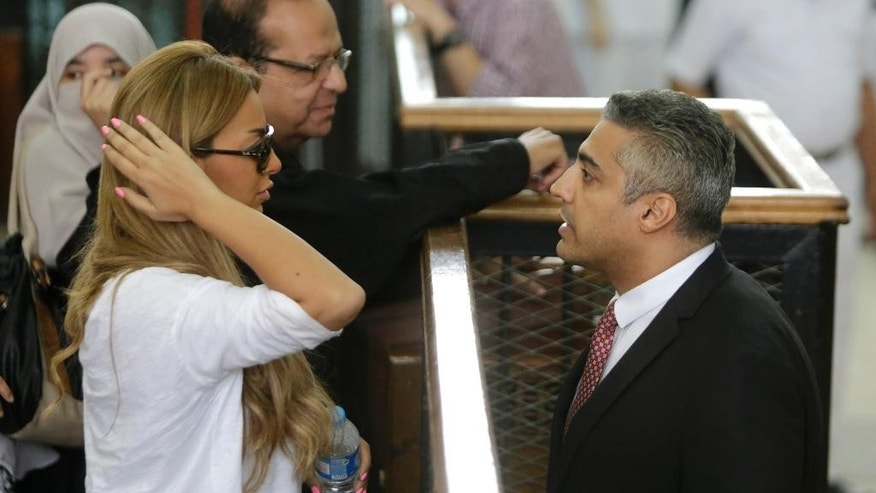 Canadian Al-Jazeera English journalist Mohammed Fahmy, talks to his fiancé Marwa Omara during his retrial at a courtroom, in Tora prison, in Cairo, Egypt, Thursday, June 4, 2015.  Fahmy is being tried along with Egyptian producer Baher Mohammed on charges accusing them of being part of a terrorist group and airing falsified footage intended to damage national security. The retrial in a case widely criticized by human rights organizations and media groups has been postponed to June 11. (AP Photo/Amr Nabil)