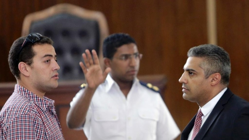 An Egyptian policeman directs Canadian Al-Jazeera English journalist Mohammed Fahmy, right, and his Egyptian colleague Baher Mohammed, left,  as they wait for their retrial in front of a policeman at a courtroom, in Tora prison, in Cairo, Egypt, Thursday, June 4, 2015. Fahmy is being tried along with Egyptian producer Baher Mohammed on charges accusing them of being part of a terrorist group and airing falsified footage intended to damage national security. The retrial in a case widely criticized by human rights organizations and media groups has been postponed to June 11. (AP Photo/Amr Nabil)