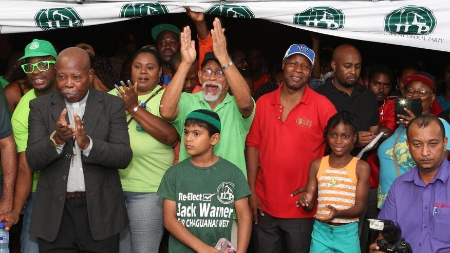 Supporters cheer for former FIFA vice president Jack Warner as speaks at a political rally in Marabella, Trinidad and Tobago, Wednesday, June 3, 2015.  Indicted on charges of racketeering, wire fraud and money-laundering, Warner is officially an internationally wanted man. In Trinidad, they've heard this all before, many times, though many residents of his homeland say that if Warner amassed his riches without taking from them, then they're fine with the arrangement. (AP Photo/Anthony Harris)
