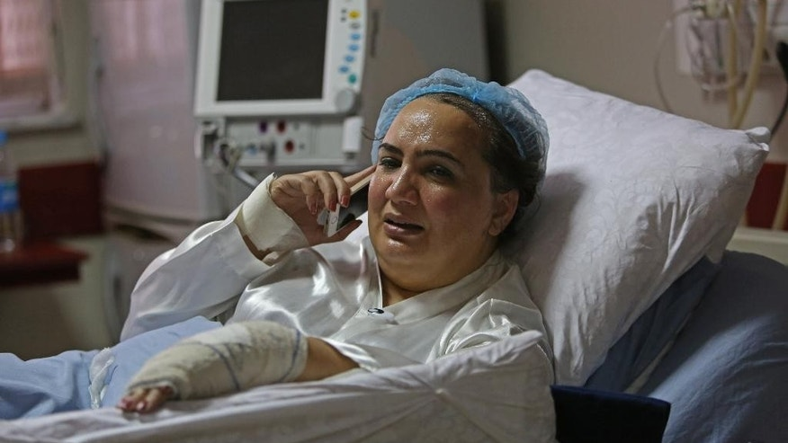 FILE - In this Sunday, Nov. 23, 2014 file photo, Afghan lawmaker Shukria Barakzai talks on her mobile phone at a government hospital she was taken into after a suicide attack targeting her motorcade in Kabul, Afghanistan. In an unprecedented step, representatives of the Taliban met this week with a delegation of female Afghan lawmakers and peace negotiators, including Barakzai , according to the Afghan government and the Taliban. The meetings, which conclude Friday, June 5, 2015 in the Norwegian capital Oslo, are part of a long-term Afghan peace initiative sponsored by Norway.  (AP Photo/Rahmat Gul, File)