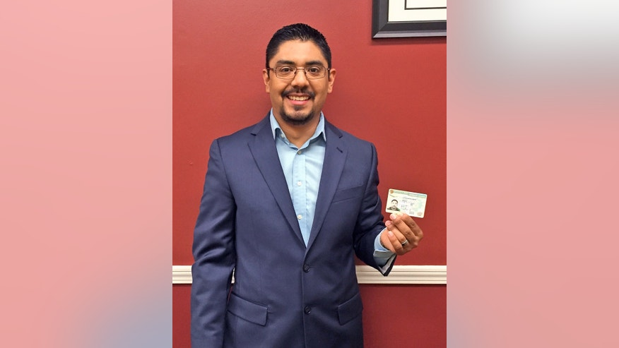 In this photo provided by Amairani Serna, lawyer Sergio Garcia holds up his green card at his law office in Chico, Calif., Thursday, June 4, 2015. Garcia, a Northern California attorney who successfully fought a high-profile battle to practice law despite his immigration status, can now live in the country legally. Sergio Garcia got his green card Thursday. That means Garcia can practice law _ and live _ in the United States without fear of arrest and deportation to his native Mexico. (Amairani Serna via AP)