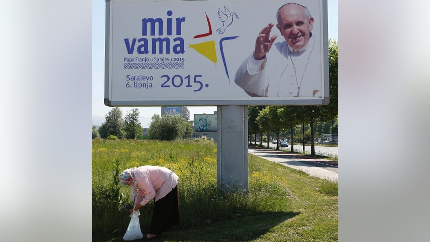 A Bosnian woman stands in front of a poster with the image of Pope Francis, ahead of his visit,  in Sarajevo, Wednesday, June 3, 2015. (AP Photo/Amel Emric)