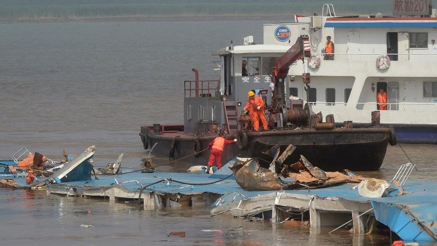 In this photo released by China's Xinhua News Agency, rescuers work on the top of the capsized Eastern Star after being righted by cranes on the Yangtze River in Jianli county of southern China's Hubei province Friday, June 5, 2015. Top-deck cabins poked out of the water from the capsized river cruise ship on the river after disaster teams righted the vessel to quicken the search for the missing people. (Xiao Yijiu/Xinhua via AP) NO SALES