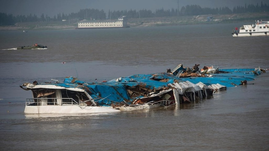 This photo released by China's Xinhua News Agency shows the capsized Eastern Star after being righted by cranes on the Yangtze River in Jianli county of southern China's Hubei province Friday, June 5, 2015. Top-deck cabins poked out of the water from the capsized river cruise ship on the river after disaster teams righted the vessel to quicken the search for the missing people. (Xiao Yijiu/Xinhua via AP) NO SALES