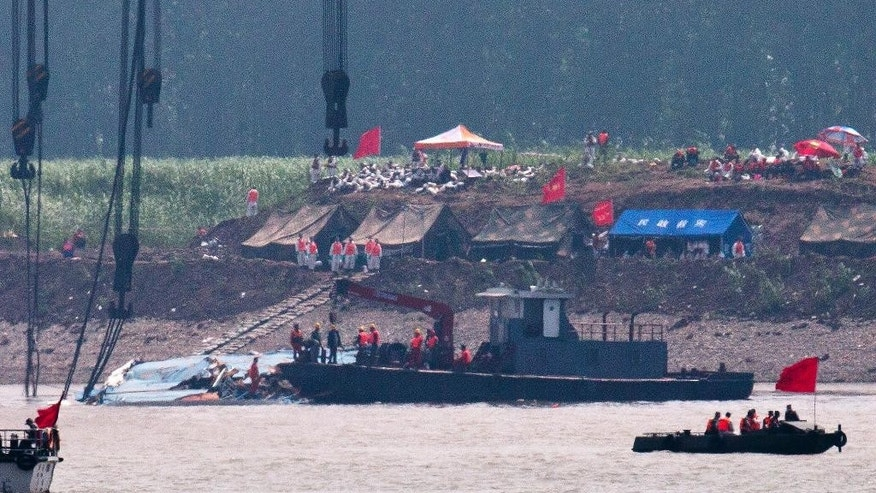 Rescuers prepare near the capsized ship Eastern Star after it was righted by cranes on the Yangtze River in Jianli county of southern China's Hubei province, as seen from across the river from Huarong county of southern China's Hunan province, Friday, June 5, 2015. The boat was righted and teams would still try to lift the vessel even though the water inside it was weighing it down. Transport Ministry spokesman Xu Chengguang said earlier that the operation would involve divers putting steel bars underneath the ship, which would then be lifted by two 500-ton cranes. (AP Photo/Andy Wong)