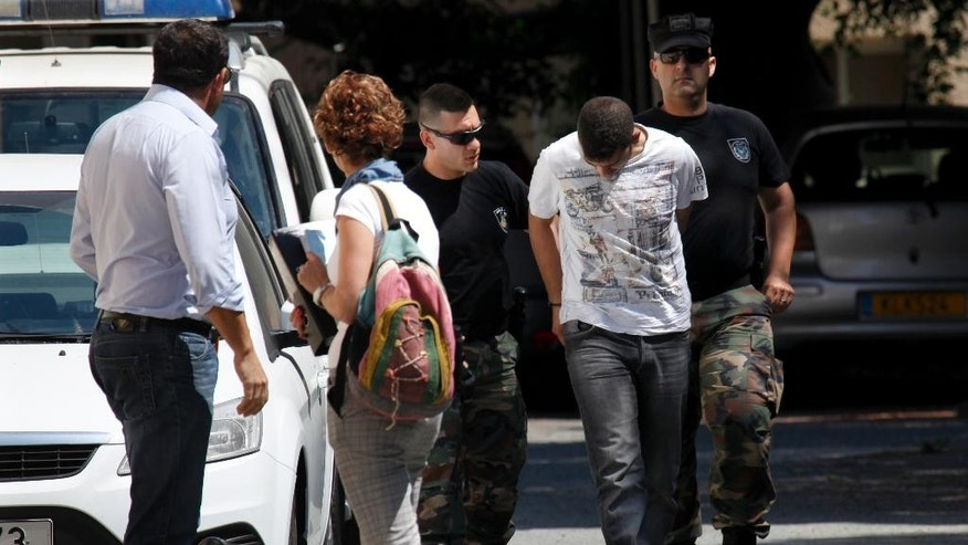Cyprus riot police escort a 26-year-old Lebanese-Canadian man who was arrested after authorities seized 5 tons of a chemical compound that can be turned into an explosive from a home he was staying in, outside a courthouse in Larnaca, Cyprus on Friday, June 5, 2015. A Larnaca court ordered that the suspect remain in police custody for another eight days in connection with the case. (AP Photo/Petros Karadjias)