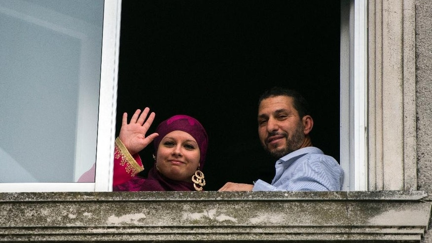 Former Guantanamo detainee Adel bin Muhammad El Ouerghi of Tunisia, stands next to his bride Roma Blanco as she wave to the press, after a religious ceremony at their home in Montevideo, Uruguay, Friday, June 5, 2015. El Ouerghi wed Friday afternoon in a religious ceremony. Blanco said Friday that they would take out a wedding license next week. Having a license is required in Uruguay for a union to be recognized. (AP Photo/Matilde Campodonico)
