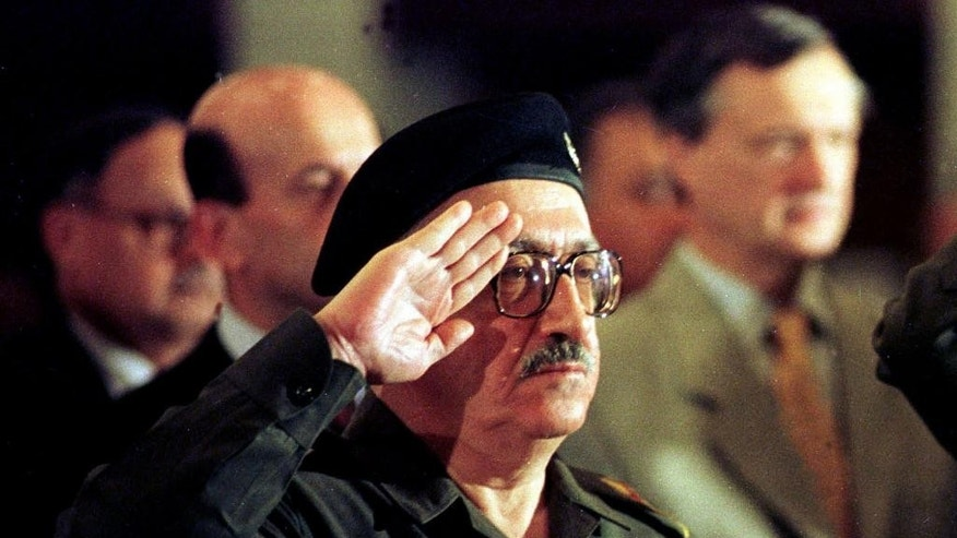 FILE - In this Dec. 2, 1998 file photo, former Iraqi foreign minister Tariq Aziz stands to attention as the Iraqi national anthem is played at a conference in Baghdad, Iraq. Officials say Aziz has died in a hospital in southern Iraq on Friday, June 5, 2015.  (AP Photo/Peter Dejong, File)