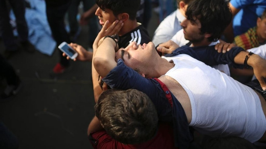 People carry a youth, wounded during an explosion at a pro-Kurdish People's Democratic Party (DHP) rally in Diyarbakir, southeastern Turkey, Friday, June 5, 2015 ahead of the general election on June 7, 2015. At least 10 people were injured in two explosions five minutes apart at the rally, attended by thousands of people, witnesses and reports said. The explosions occurred at the party's final election rally in Diyarbakir _ the main city in Turkey's predominantly Kurdish southeast _ as the party's leader Selahattin Demirtas was preparing to address the crowd. (AP Photo/Emre Tazegul)
