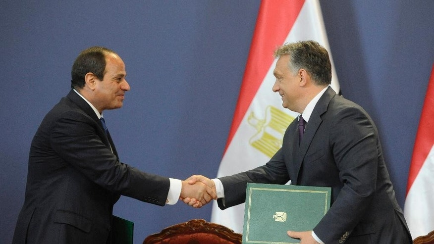 Egyptian President Abdel Fattah el-Sissi, left, shakes hands with Hungarian Prime Minister Viktor Orban during a signing ceremony in the Parliament building in Budapest, Hungary, Friday, June 5, 2015. El-Sissi is staying on a two-day visit in Hungary. (Zoltan Mathe/MTI via AP)