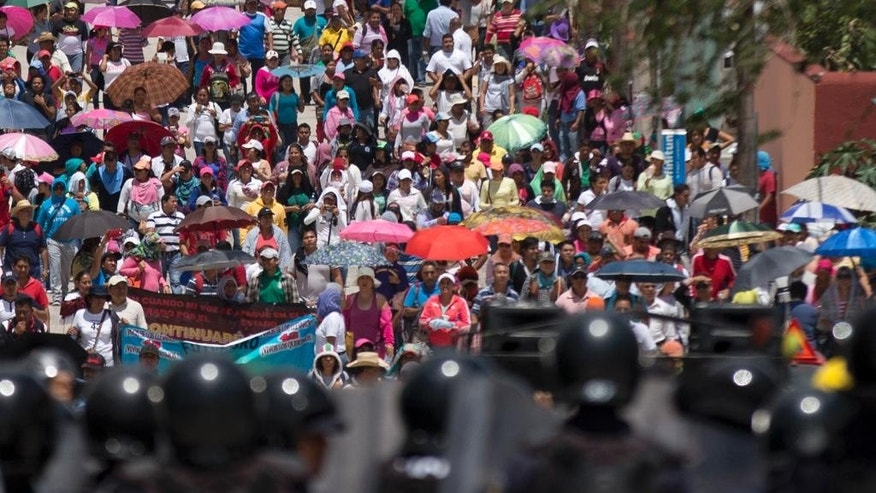 Members of a teachers union march towards scores of police in riot gear surrounding the office of the National Electoral Institute, in Chilpancingo, Guerrero State, Mexico, Friday, June 5, 2015. The confrontation ended peacefully. Radical groups and unionized teachers have vowed to block Sunday's voting for the lower house of congress, nine governorships and hundreds of mayorships. (AP Photo/Rebecca Blackwell)