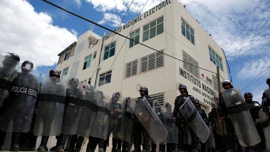 Federal police surround the offices of the National Electoral Institute, during a protest by members of a teachers union in Chilpancingo, Guerrero State, Mexico, Friday, June 5, 2015. The confrontation ended peacefully. Radical groups and unionized teachers have vowed to block Sunday's voting for the lower house of congress, nine governorships and hundreds of mayorships. (AP Photo/Rebecca Blackwell)